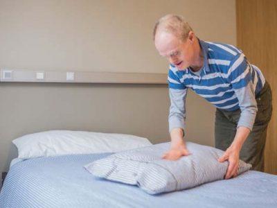 una persona con síndrome de Down haciendo la cama