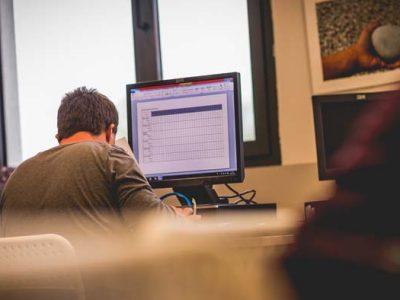 Joven con discapacidad trabajando competencias informáticas